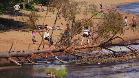Little girl on a fallen tree moved across the rive Footage