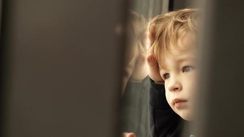 Little boy looking out of the window Footage