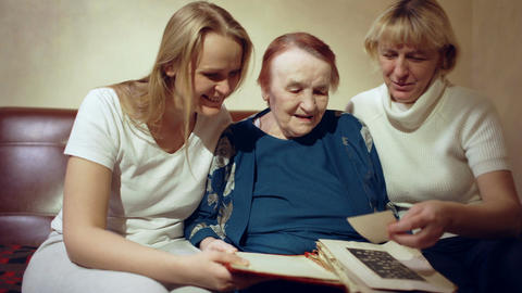 Three women looking through the family archive Footage
