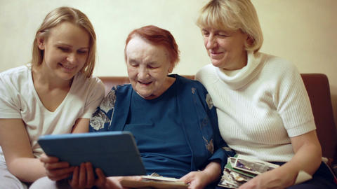 Family of three women looking photos on touchpad Stock Video Footage