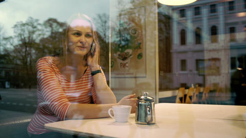 Woman talking on mobile phone in cafe Footage