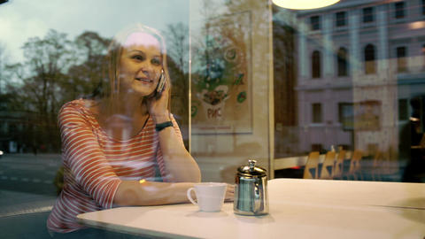 Woman talking on mobile phone in cafe Stock Video Footage
