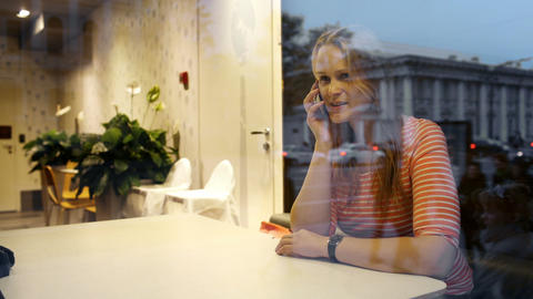 Evening phone talk of a young woman in cafe Stock Video Footage