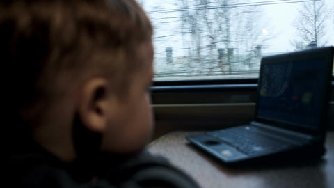 Boy watching movie or cartoon on laptop in the tra Stock Video Footage