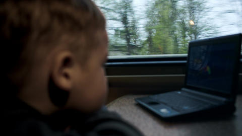 Boy watching movie or cartoon on laptop in the tra Footage