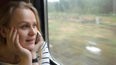 Young woman talking on the phone while traveling b Footage