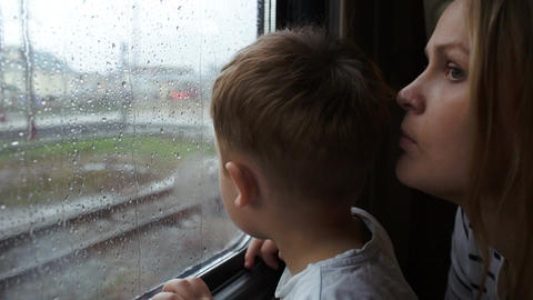 Boy and his mother looking out the window of train Footage