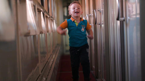 Happy boy running along the train hallway Stock Video Footage
