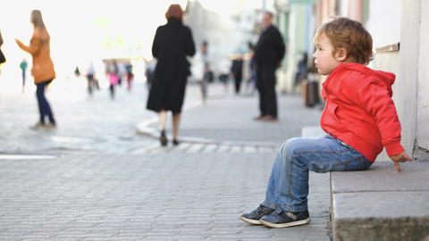 Little boy sitting alone in the street, people pas Live Action
