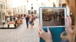 Woman with tablet making video of street in Tallin Footage