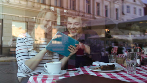 Happy young couple with tablet pc in a cafe Footage