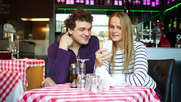 Young couple in cafe having a video chat on smartp Stock Video Footage