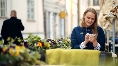 Woman using her smartphone sitting in outdoor cafe Footage