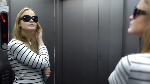 Young woman in the lift primping and make funny fa Stock Video Footage