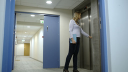 Young woman calling and waiting for elevator Footage