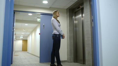 Young woman calling and waiting for elevator Stock Video Footage