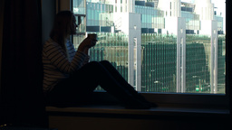 Woman drinking coffee on the windowsill with city  Footage