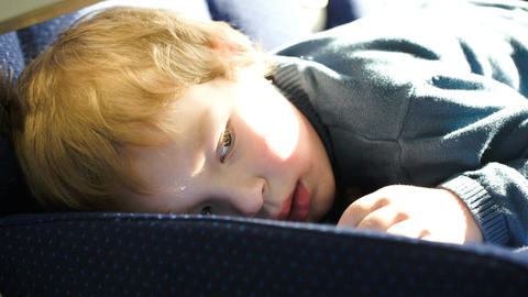 Little boy lying on the seat in the bus, car ot tr Stock Video Footage