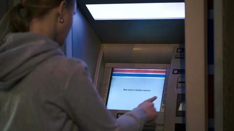 Woman using atm outdoor in the evening Live Action