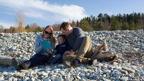 Family of three sitting on the stony shore and wat Footage