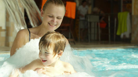 Mother holding son splashing in the rough water of Stock Video Footage
