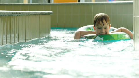 Boy with rubber ring swimming in water labyrinth Footage
