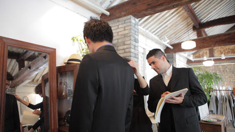 Italian Tailor Helping Chinese Customer In Boutiqu stock footage
