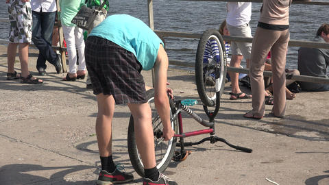 The young man looks at the bike. 4K Footage