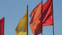 Red and yellow flags are fluttering in the sky Footage