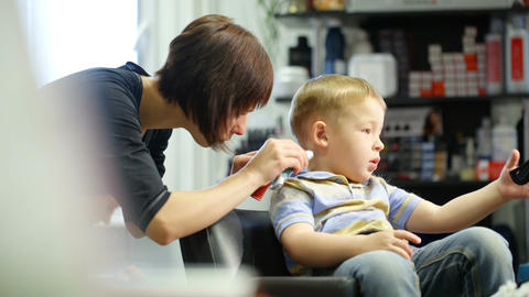 Little boy during haircut at the hairdressing salo Footage