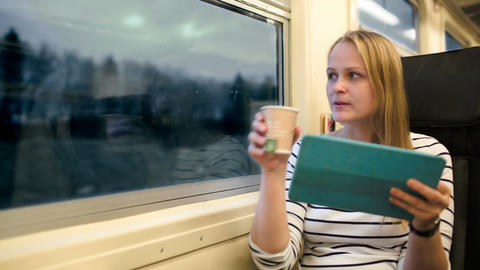 Woman with touchpad and tea in the train in the ev Footage