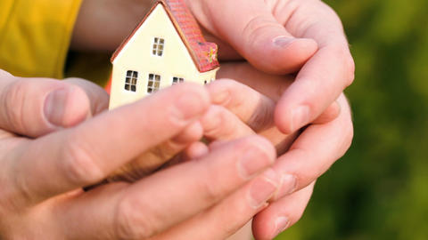 Couple holding a small toy house in hands Live Action