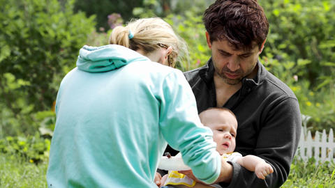 Young parents feeding a baby boy outdoor Footage