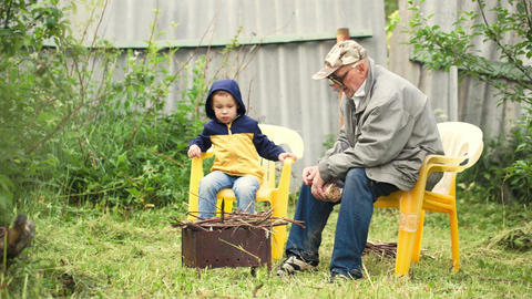 Grandson and grandfather sitting by the fire in th Footage