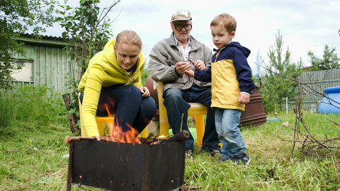 Mother, son and grandpa by the fire in the yard Footage