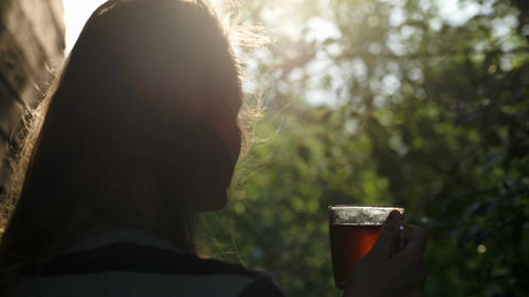 Woman having tea outdoor during sunset Footage