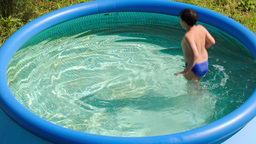 Boy having fun in outdoor pool on a hot summer day Stock Video Footage
