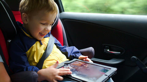 Little boy playing on tablet computer in the car Footage
