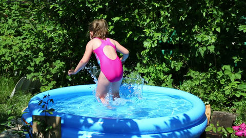 cheerful girl in inflatable pool in summer garden Footage