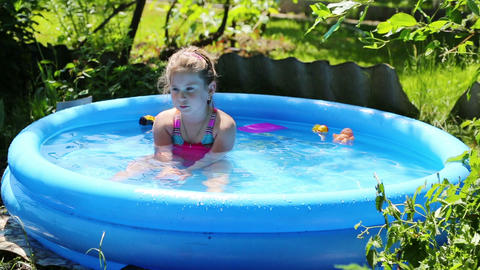 cheerful girl in inflatable pool in summer garden Stock Video Footage