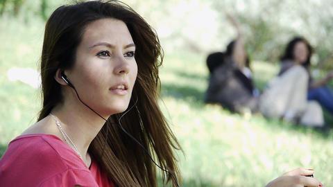 Girl sitting listening outdoor grass Stock Video Footage