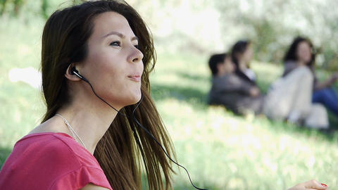 Girl sitting listening outdoor grass Stock Video Footage
