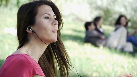 Girl sitting listening outdoor grass Footage