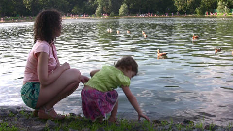 mother with girl and ducks on pond Footage