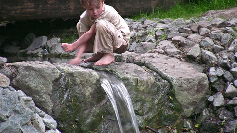 child play on small waterfall Footage