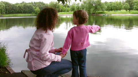 mother with little girl on pond Footage