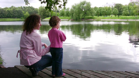 mother with children on pond Stock Video Footage