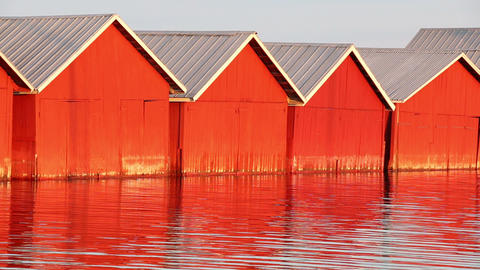 Red wooden boathouses at lakeside Stock Video Footage