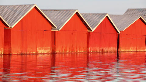 Red wooden boathouses at lakeside Footage