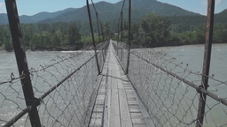 Walking on a suspension bridge across the turb Footage